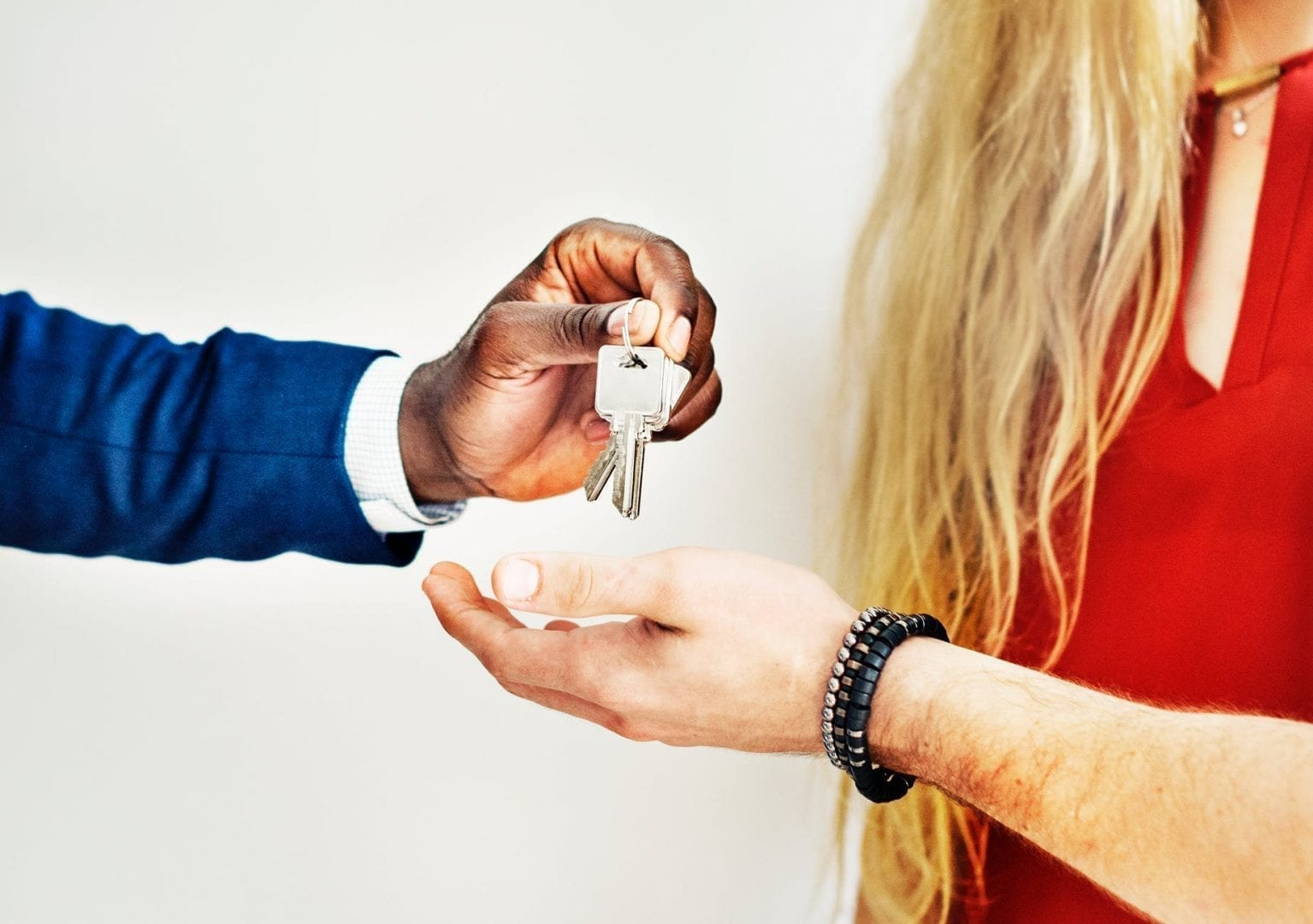 a black estate agent handing over keys to a young blonde woman and her partner